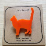 Cat brooch laser cut from orange acrylic